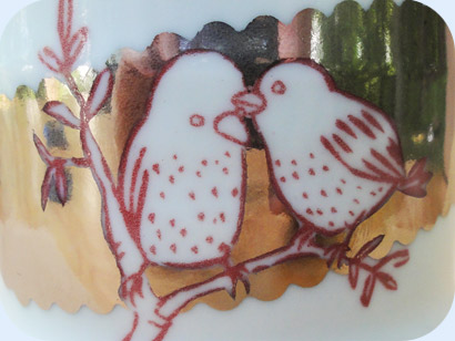 Detail shot of red birds drawn in porcelain with sliver background